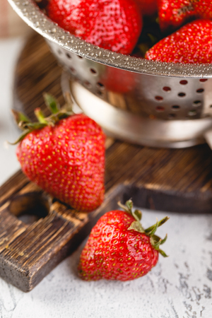 Fresh berries strawberries in a while colander on grey background Archivio Fotografico