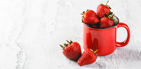 Fresh Strawberries in red enamel cup on grey background. Space for text. Long wide banner