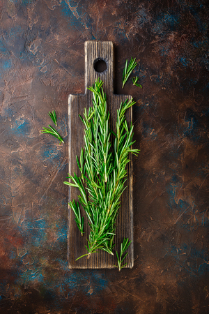 Fresh Rosemary bound on a wooden cutting board. Top view.