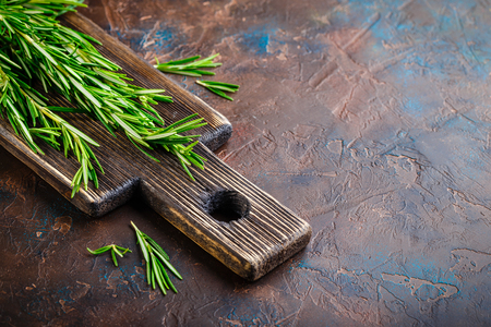 Fresh Rosemary bound on a wooden cutting board. Space for text.