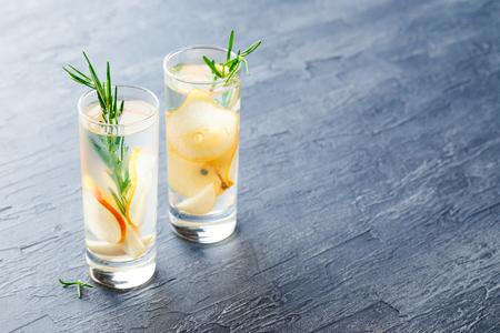 夏日饮品,迷迭香梨鸡尾酒加冰n杯。清爽的夏天自制酒精或非酒精鸡尾酒或排毒注入调味水。空间的文本。