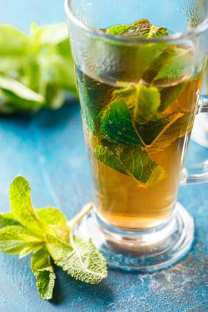 Hot tea with mint leaves in glass cups on a blue background. Herbal Tea