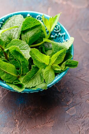 Fresh mint leaves in the ceramic bowl on the broun concrete background. Healthy vegetarian food concept. Close up. Place for text