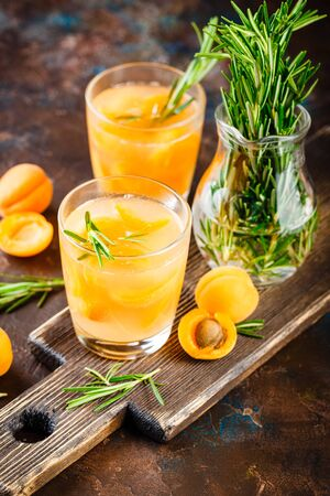 Summer drinks, rosemary aprcot cocktails with ice in glasses. Refreshing summer homemade Alcoholic or non-alcoholic cocktailsor Detox infused flavored water