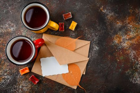Two colored enamel cups of tea, two envelops, watercolors in cuvettes, , autumn leaves and bumps on a rusty brown background