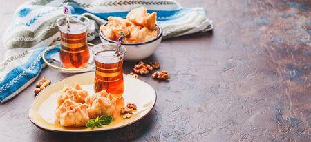 Middle Eastern or Arabic tea with mint in a traditional glass cup and Turkish delight Baklava. Ramadan kareem. Eid mubarak. Islamic holidays decoration.
