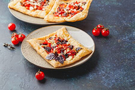 Puff pastry tartlets with tomatoes, sweet bell peppers, salami, feta cheese and purple basil.