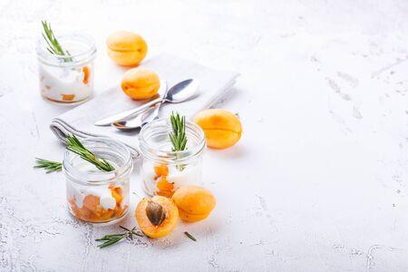 Natuurlijke yoghurt met stukjes abrikozen, walnoot en rozemarijn in mini glazen potten op lichte achtergrond.