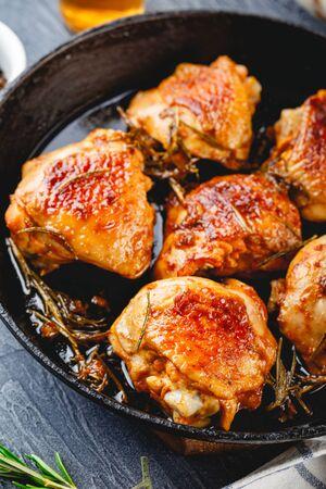 Cosce di pollo fritte al rosmarino in una padella di ghisa, pomodorini e rosmarino sullo sfondo, vista dall'alto Archivio Fotografico