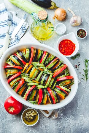 Vegetarian uncooked ratatouille from eggplants, zucchini, tomatoes and bell pepper sauce and tomato with herbs in ceramic form before baking. Top view. Rustic style.