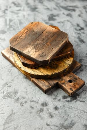 Stack of different wooden cutting boards on grey background. 写真素材