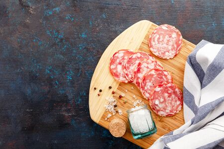 Wooden cutting board and pieces of Salchichon on dark table