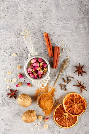 Different kinds of spices - cinnamon, anise stars, cloves, walnuts, dried orange slices, caramelized brown sugar and dried rose buds on a gray concrete background. Top view with copy space