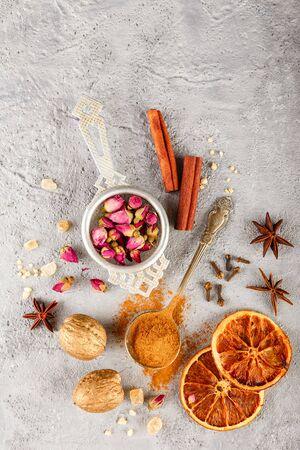 Verschiedene Gewürze - Zimt, Anissterne, Nelken, Walnüsse, getrocknete Orangenscheiben, karamellisierter brauner Zucker und getrocknete Rosenknospen auf grauem Betonhintergrund. Draufsicht mit Kopienraum Standard-Bild