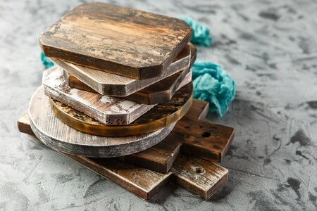 Stack of different wooden cutting boards on grey background.