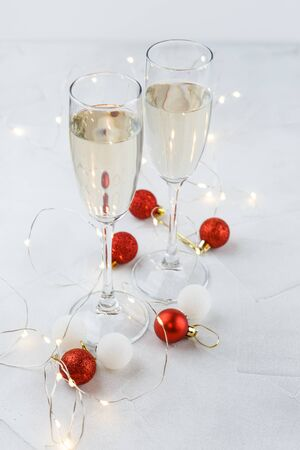 Composition for Christmas with red and white balls, white lights and two glasses of champagne