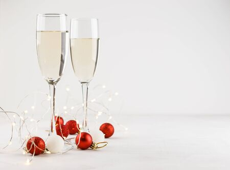 Composition for Christmas with red and white balls, white lights and two glasses of champagne. Space for text.