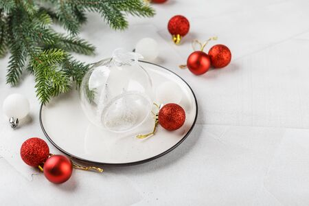 Festive place setting for christmas dinner on white rustic background. Christmas table setting with red and white decorations. Copy space.