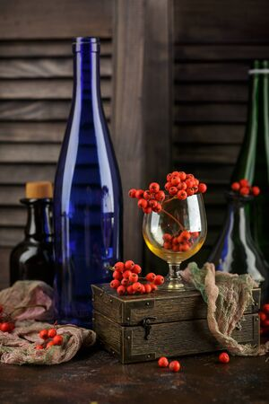 Autumn still life with rowan berries, a glass glass, bottles of wine and a wooden box on a dark background 写真素材