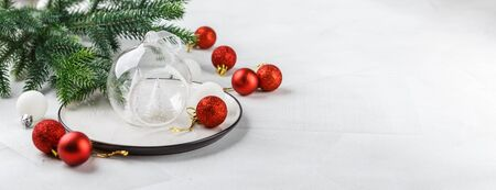 Festive place setting for christmas dinner on white rustic background. Christmas table setting with red and white decorations. Copy space. Long wide banner