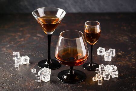 Set of strong alcoholic drinks in glasses in assortent: cognac, brandy and whiskey.