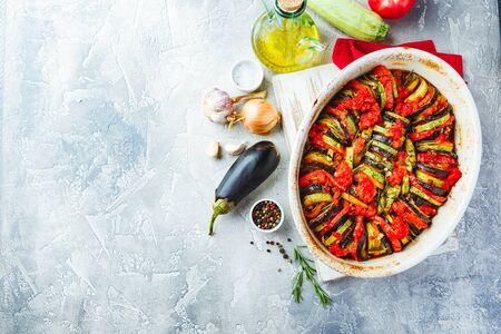 Vegetarische ratatouille van aubergines, courgettes, tomaten en paprikasaus en tomaat met kruiden in keramische vorm voor het bakken. Bovenaanzicht. Rustieke stijl. Stockfoto