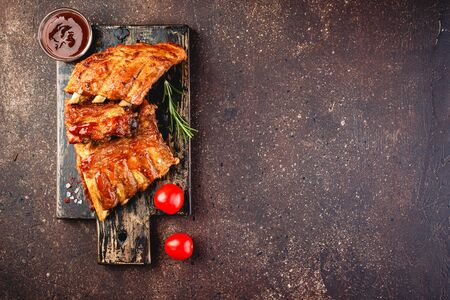 Grilled pork ribs on a wooden cutting board on a brown background. Top view. Space for text.