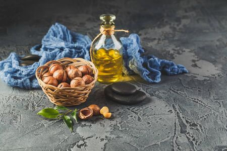 Glass bottles with Natural macadamia oil with macadamia nuts, sea salt and zen stones. Superfood and healthy food concept