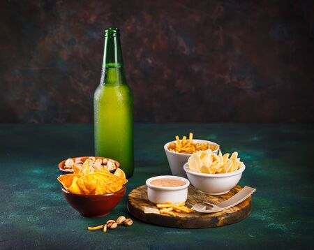 Glass mug with beer with foam and water drops and snacks on a dark green background