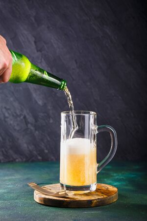 Glass mug with beer with foam and water drops on a dark green background 写真素材
