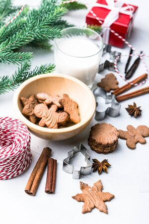 Homemade delicious Christmas gingerbread cookies with glass of milk, spices, cinnamon and anise stars, metall cutters and gift on the white background.