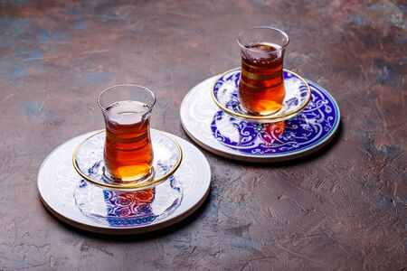 Traditional Turkish black tea in glass at decorative plates on concrete background
