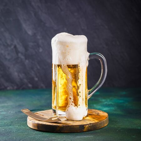 Glass mug with beer with foam and water drops on a dark green background Imagens