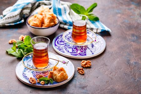 Middle Eastern or Arabic tea with mint in a traditional glass cup and Turkish sweetness Baklava. Ramadan kareem. Eid mubarak. Islamic holidays decoration. Imagens - 129862335