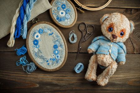 Two embroideries in decorative frames, accessories for embroidery, and Teddy bears toy on wooden background 写真素材