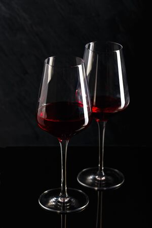 Wine bottle and glasses of red wine in low key on black background