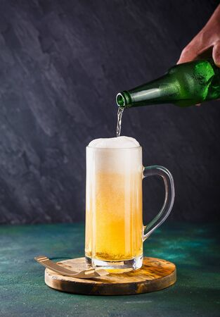 Glass mug with beer with foam and water drops on a dark green background Stock Photo
