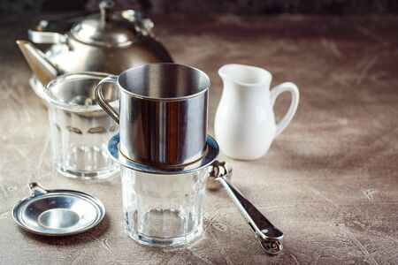 Vietnamese coffee in glass cups and traditional metal coffee maker phin. Traditional method of making of vietnamese coffee. Space for text. Stock Photo