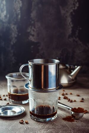 Vietnamese coffee in glass cups and traditional metal coffee maker phin. Traditional method of making of vietnamese coffee