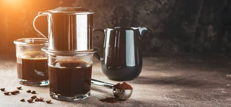 Vietnamese coffee in glass cups and traditional metal coffee maker phin. Traditional method of making of vietnamese coffee. Long wide banner. Space for text. Stock Photo