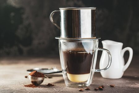 Vietnamese coffee with condensed milk in glass cups and traditional metal coffee maker phin. Traditional method of making of vietnamese coffee