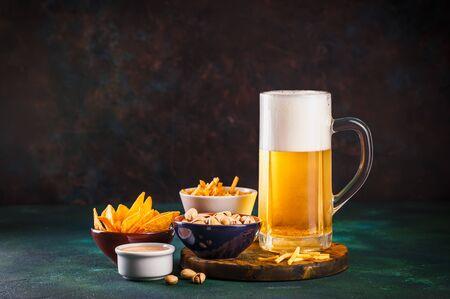 Glaskrug mit Bier mit Schaum und Wassertropfen und Snacks auf dunkelgrünem Hintergrund