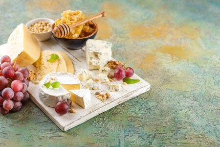 Different types of cheese, red grapes, honeycomb and nuts on a white cutting board. Place for text