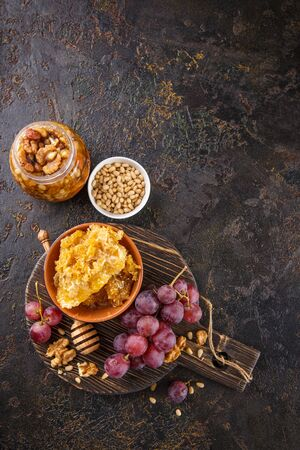 Grapes, honey and nuts over wooden cutting board. Top view with copy space. Reklamní fotografie