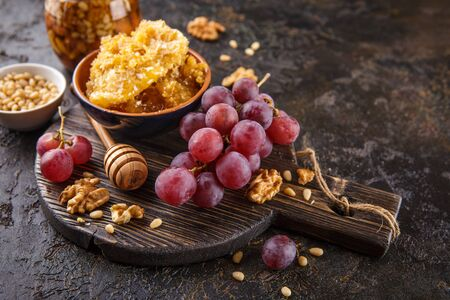 Grapes, honey and nuts over wooden cutting board. Reklamní fotografie