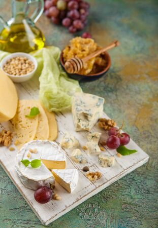 Different types of cheese, red grapes, honeycomb and nuts on a white cutting board