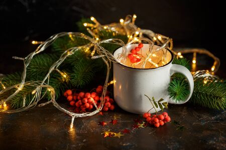 Christmas glowing garland in cupp, spruce branches and rowan berries on dark background