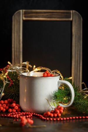 Christmas glowing garland in cup, chalk board, fir branches and rowan berries on dark background Stock Photo
