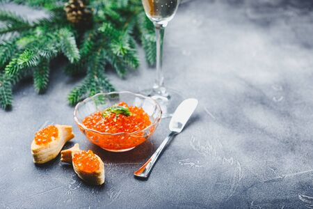Delicious puff pastry tartlets in the shape of fish with red caviar on a festive table with glasses of champagne.