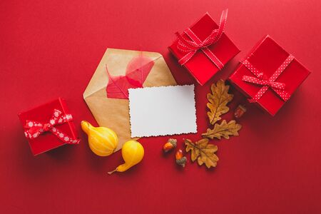 Greeting card and autumn frame of oak and sceleton leaves, red gift boxes, envelop, acorns and two small pumpkins on a red background. Flat lay, copy space.
